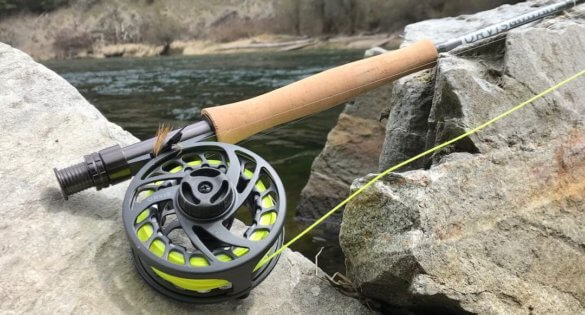 This photo shows the 9-foot 5-weight Orvis Clearwater Fly Rod and Clearwater II Reel on a rock near a river.
