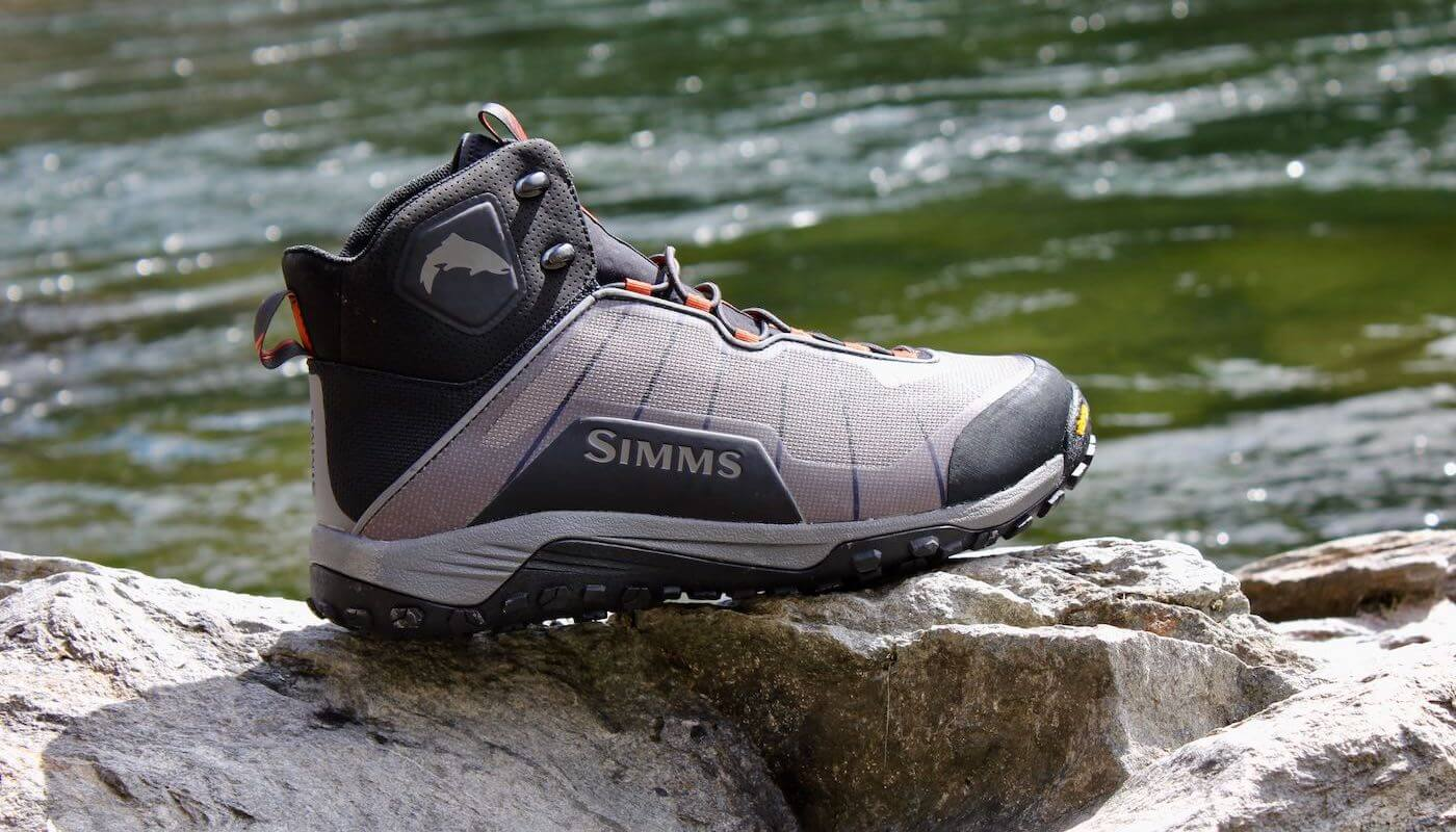 This Simms Flyweight Wading Boot Review photo shows a Simms Flyweight Wading Boot on a rock with a river in the background.