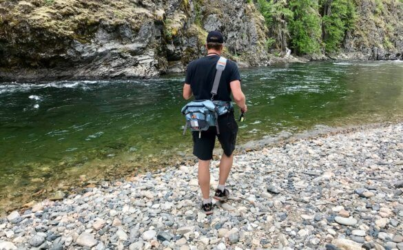 This photo shows the shoulder strap for the Umpqua Tongass 650 Waterproof Waist Pack while being worn buy a fly fisher.