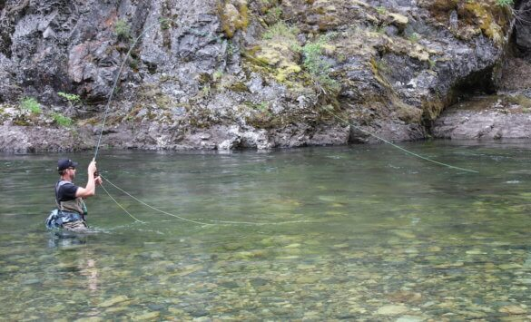 This photo shows a fly fisherman fishing in a river while wearing the Umpqua Tongass 650 Waterproof Waist Pack.