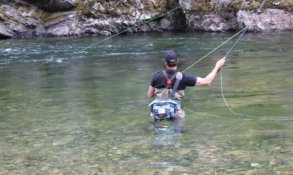 This photo shows a fly fisherman wading in a river while wearing the Umpqua Tongass 650 Waterproof Waist Pack.