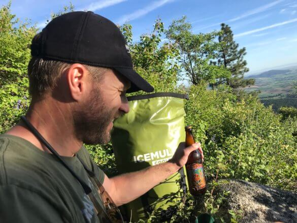 This backpack cooler guide photo shows the author with a backpack cooler and a cold drink.