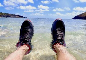 This photo shows a man wearing a pair of water shoes with his feet in the water on an ocean beach.
