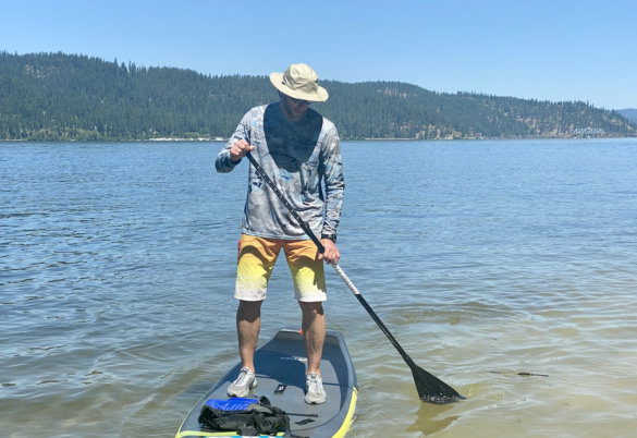 This review photo shows the author illustrating the sun protection from the Shelta Firebird V2 hat while SUP paddling.