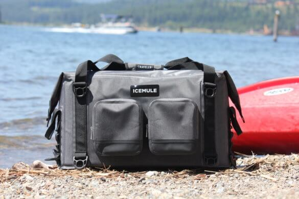 This photo shows the ICEMULE Traveler cooler near the water and near a kayak.