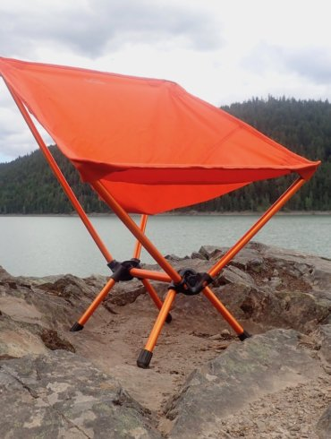 This gear review photo shows the REI Co-op Flexlite Air Chair on a rock above a lake.