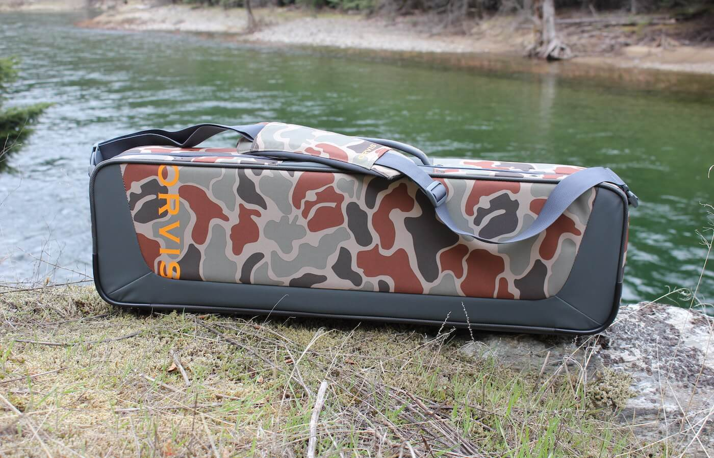 This review photo shows the Orvis Safe Passage Carry It All fly fishing travel bag case outside near a river.