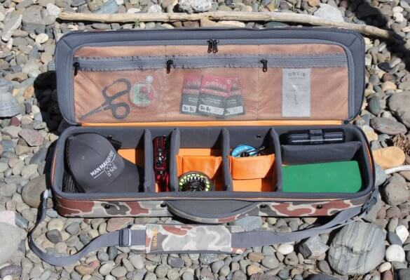 This review photo shows the Orvis Safe Passage Carry It All fly fishing travel bag case with fly fishing accessories inside of it.