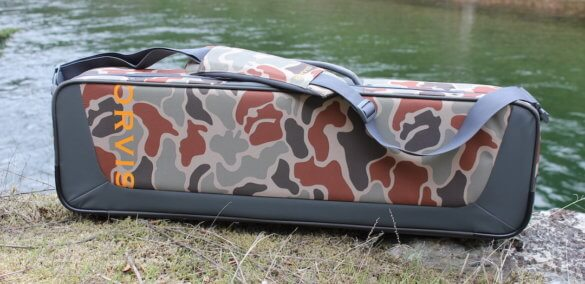 This review photo shows the Orvis Safe Passage Carry It All fly fishing travel bag case next to a river.