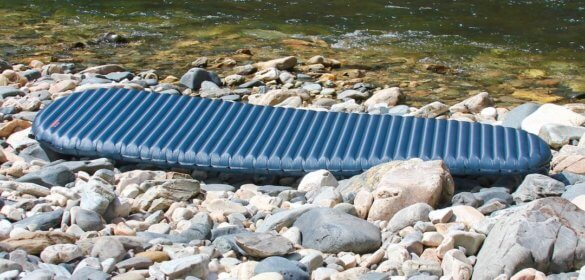 This review photo shows the full length of the Therm-a-Rest NeoAir UberLite backpacking air mattress on some rocks outside.