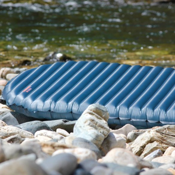 This review photo shows the Therm-a-Rest NeoAir UberLite air mattress outside on some rocks.