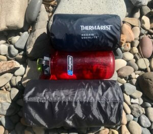 This photo shows the packed size of the Therm-a-Rest NeoAir UberLite relative to a Nalgene water bottle and the packed size of the Therm-a-Rest NeoAir Xlite air mattress.