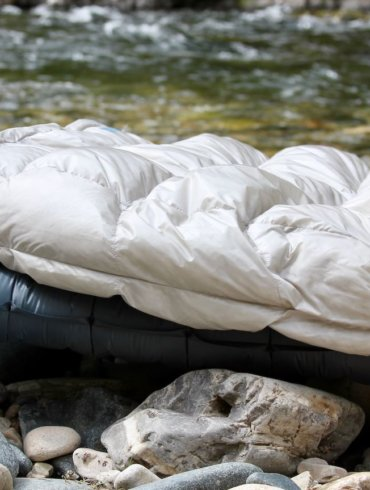 This review photo shows the Therm-a-Rest Vesper Quilt outside on top of a Therm-a-Rest NeoAir UberLite air mattress for backpacking.