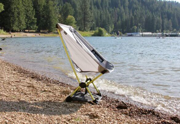 This review photo shows the Helinox Chair Zero on a beach near a lake.