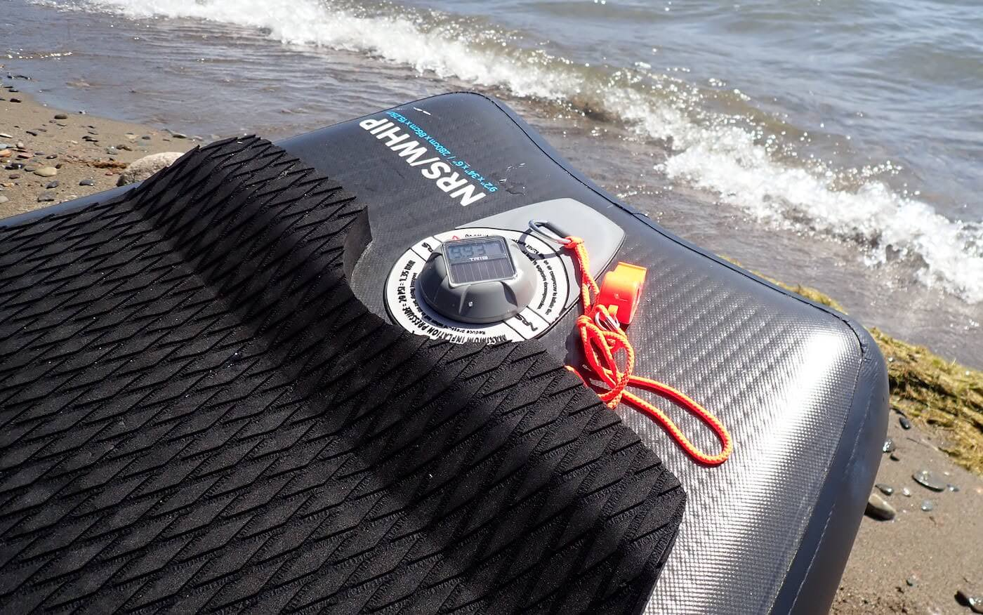 This review photo shows the TRīB airCap Pressure Gauge on an inflatable SUP paddle board on a beach.