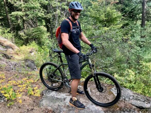 This photo shows the author with the REI Co-op Cycles DRT 1.2 mountain bike outside on a mountain trail.