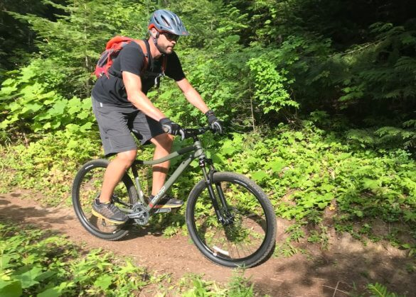 This photo shows the author riding the REI Co-op Cycles DRT 1.2 on a single-track trail.