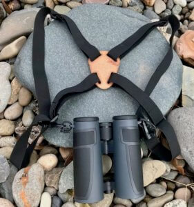 This photo shows binocular chest straps with a set of binoculars.