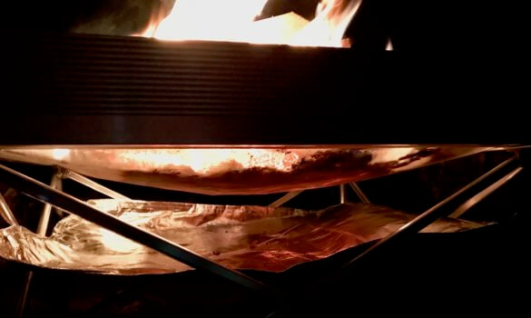 This photo shows the Heat Shield underneath a fire in the Fireside Outdoor Pop-Up Fire Pit.