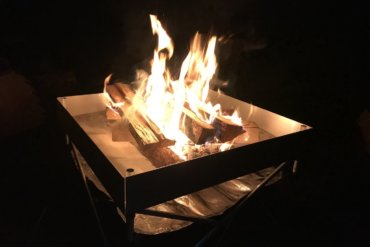 This photo shows the Fireside Outdoor Pop-Up Fire Pit with a campfire in the dark.