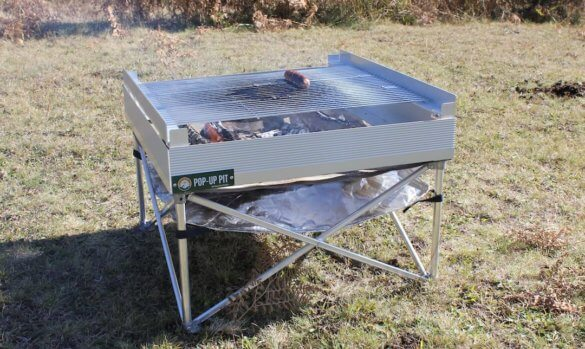 This photo shows the Fireside Outdoor Pop-Up Fire Pit with the option Tri-Fold Grill accessory.