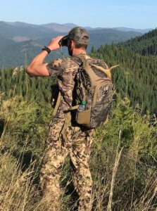 This photo shows a hunter wearing the Nexgen Outfitters Whitetail Caddy Pack outside in the woods while scouting.