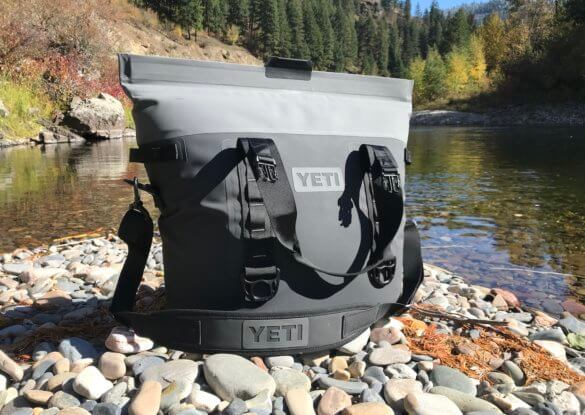 This photo shows the YETI Hopper M30 outside on rocks near a river.