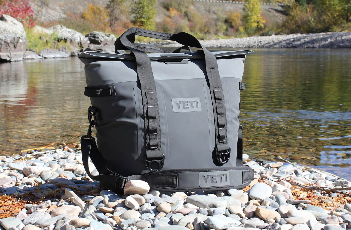 This photo shows the YETI Hopper M30 soft cooler next to a river.