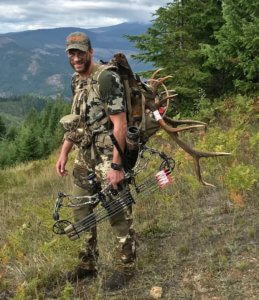 This photo shows a bowhunter with a compound bow and elk antlers in a hunting backpack.