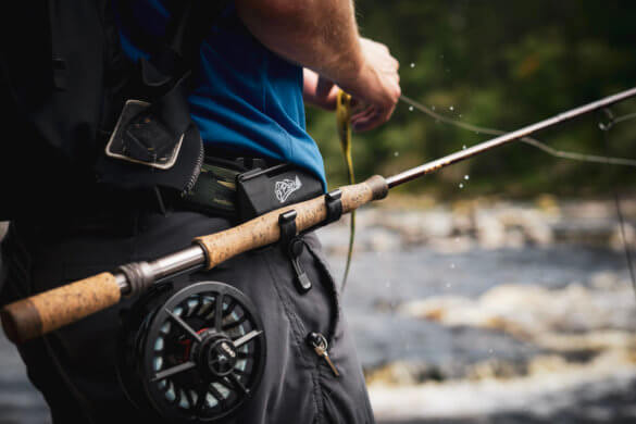 This photo shows the O'Pros 3rd Hand Rod Holder being used by a fly fisherman outside near a river.