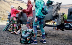 This photo shows three women fly fishers gearing up with FisheWear apparel and fishing gear.
