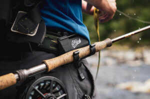 This fishing gift photo shows a fisherman wearing the O'Pros 3rd Hand Rod Holder with a fishing rod while fishing.