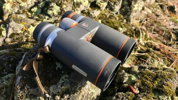 This photo shows the Maven B.1 Binocular 10x42 on a rock in the woods.