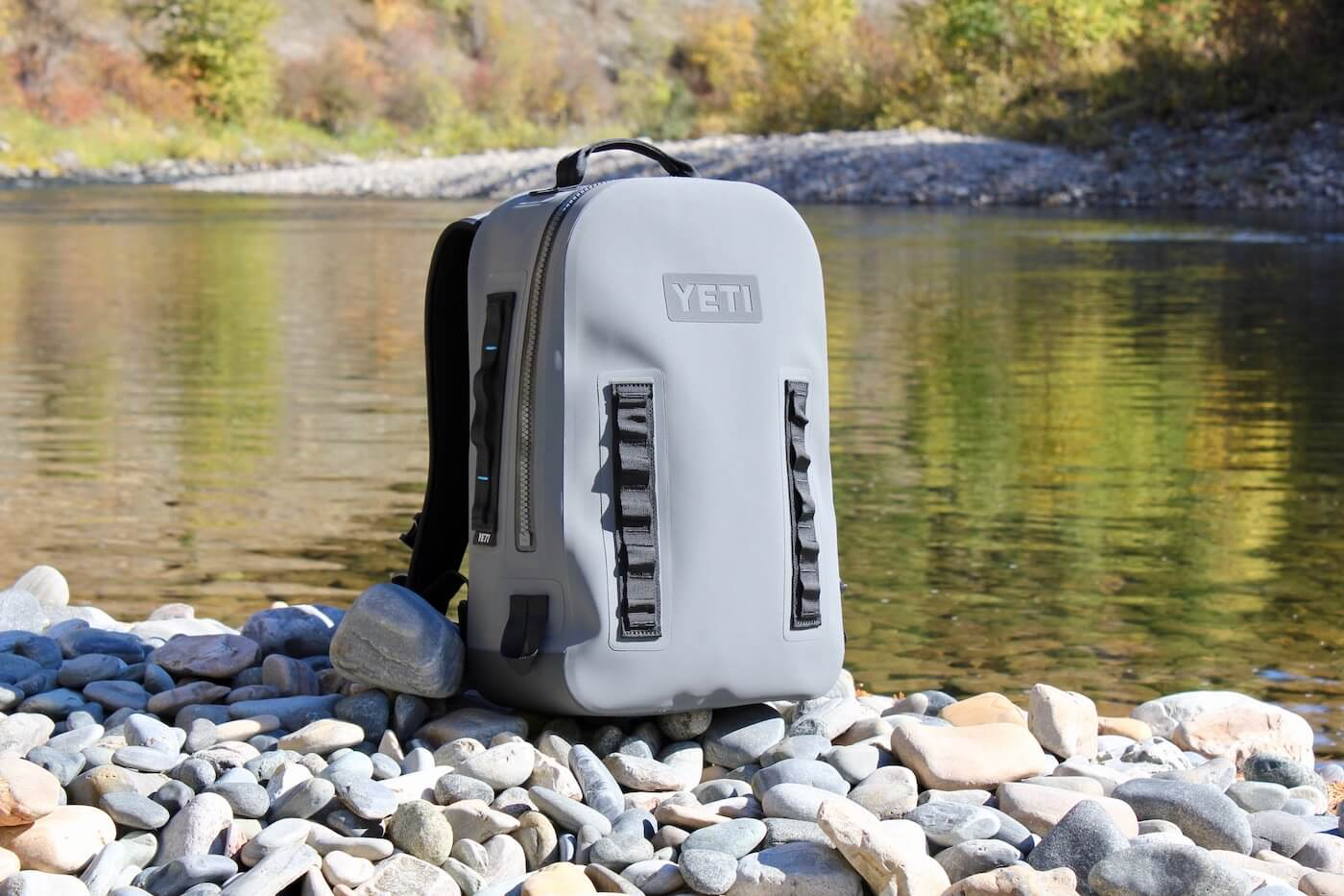 This photo shows the YETI Panga Backpack 28 on the side of a river.