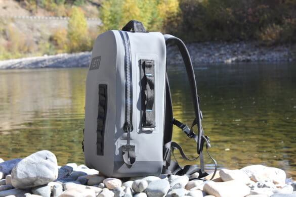 This photo shows the YETI Panga Backpack 28 from the side near a river.