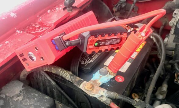 This photo shows The Zeus battery clamps attached to a car battery.