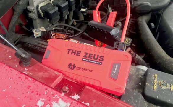 This photo shows The Zeus portable jump starter connected to a vehicle's battery.
