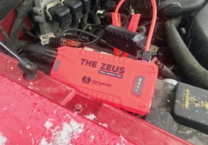 This photo shows the Uncharted Supply Co 'The Zeus' portable jump starter attached to a dead auto battery.
