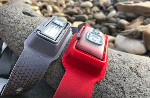 This photo shows the BioLite HeadLamp 200 next to the HeadLamp 330 on a rock.