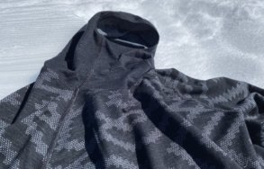This photo shows the Odlo Natural + Kinship Warm Base Layer Top with Face Mask outside on snow.