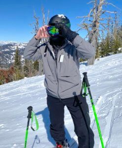 This review photo shows the Odlo Natural + Kinship Warm Base Layer Top with Face Mask being worn underneath a ski helmet and ski goggles.