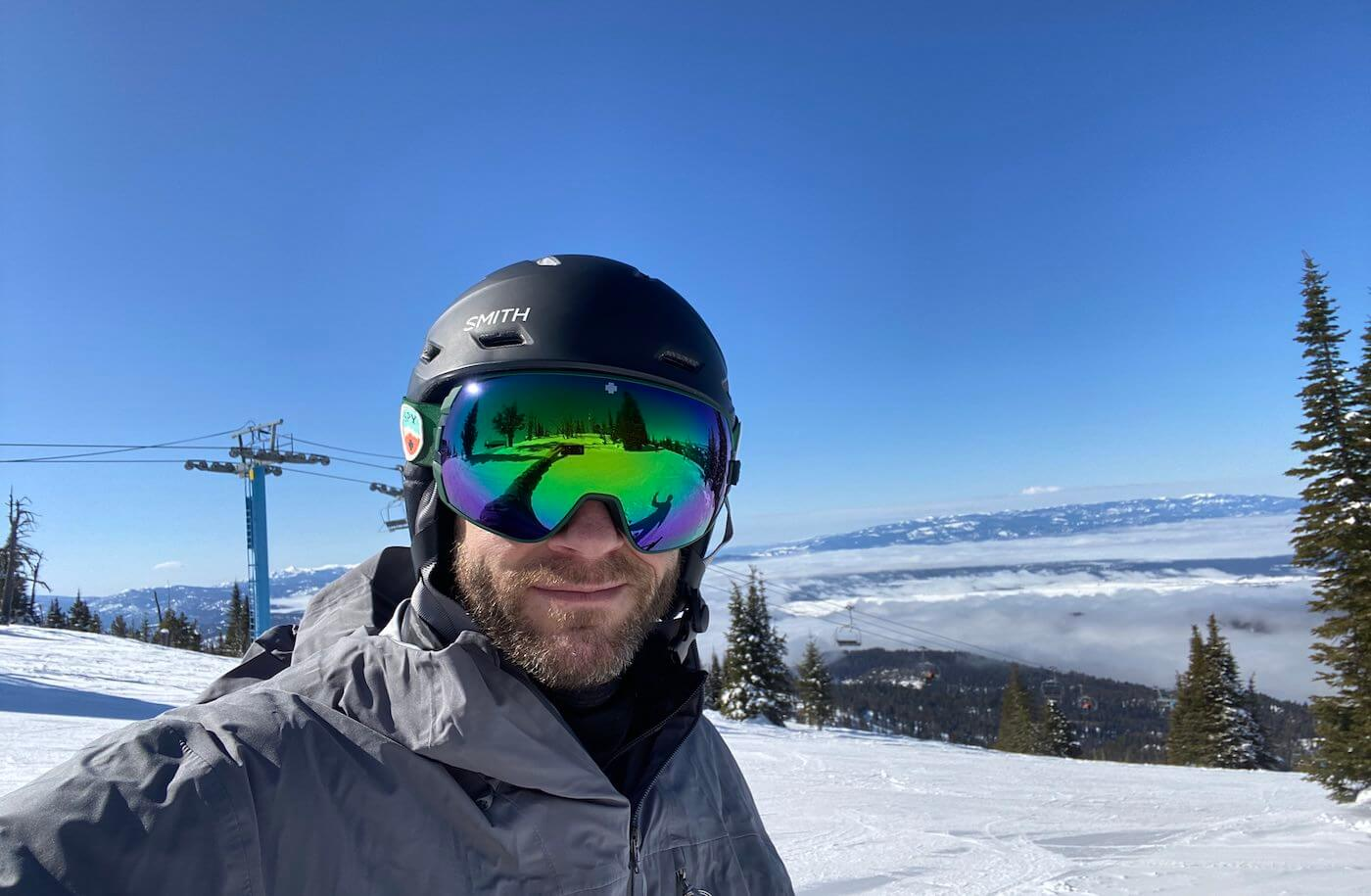 This photo shows a skier wearing the SPY Legacy Snow Goggle while outside on the ski slopes.