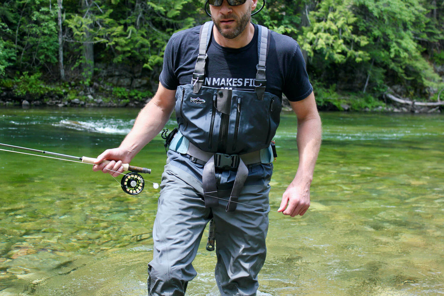 This best fishing waders image shows the author testing fishing waders on a river while fishing.