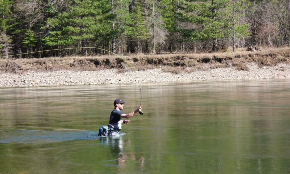 This review photo shows a fly fisher fishing with the Redington Crosswater Combo fly outfit while wading in a river.
