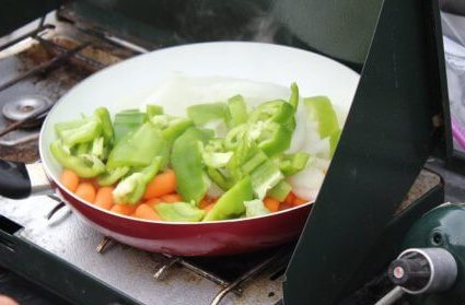 This best camping stoves photo shows a Coleman Classic Camp Stove with a frying pan with cooking vegetables.