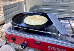 This best camping stoves photo shows a camping stove with a cooking pancake outside.