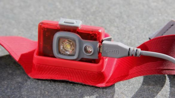 This photo shows the BioLite HeadLamp 200 with a charging cable.