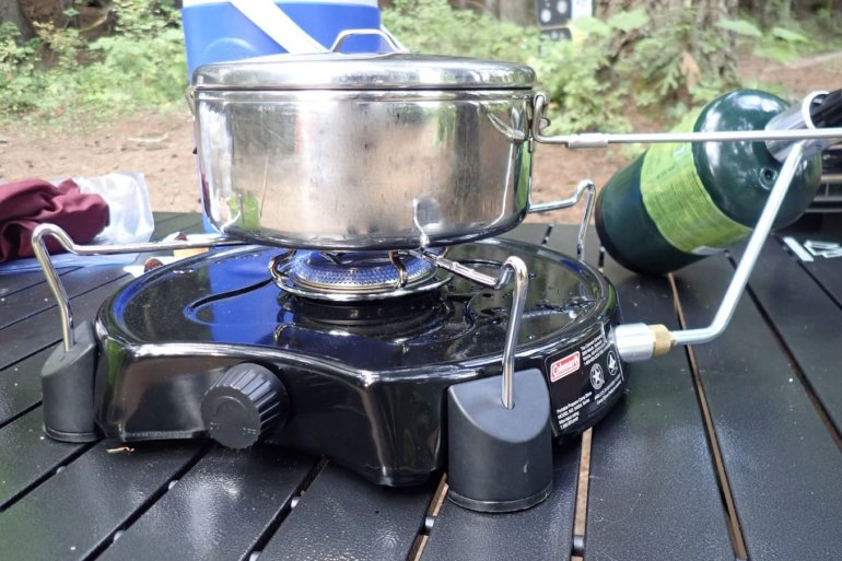 This photo shows the Coleman PowerPack Propane Stove for camping being used to cook on a camping table.
