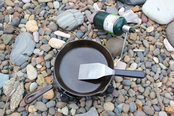 This photos shows a Coleman PowerPack Propane Stove with a cast-iron frying pan on top of it.