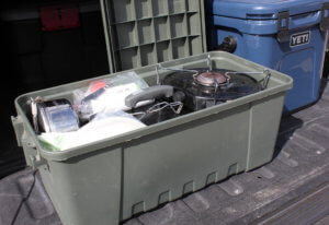 This photo shows the Coleman PowerPack Propane Camping Stove packed up in a camping box with other camp cooking gear.
